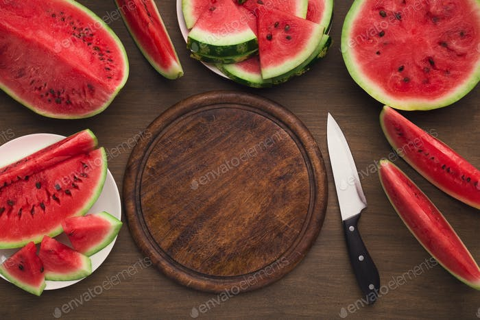 Empty wooden platter, knife and red ripe watermelon slices