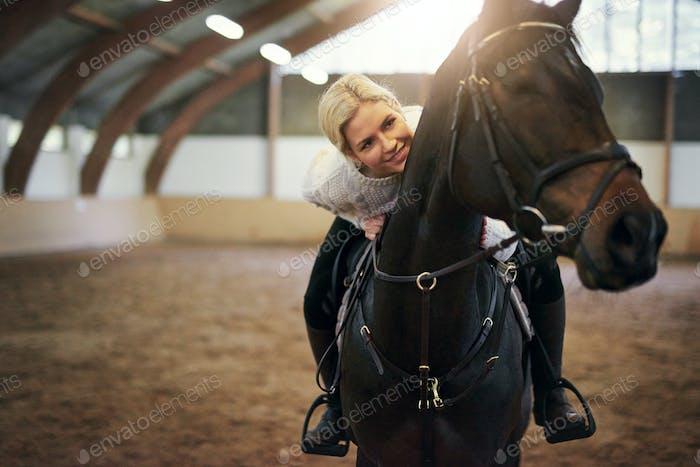Smiling blonde�female�leaning on black horseback