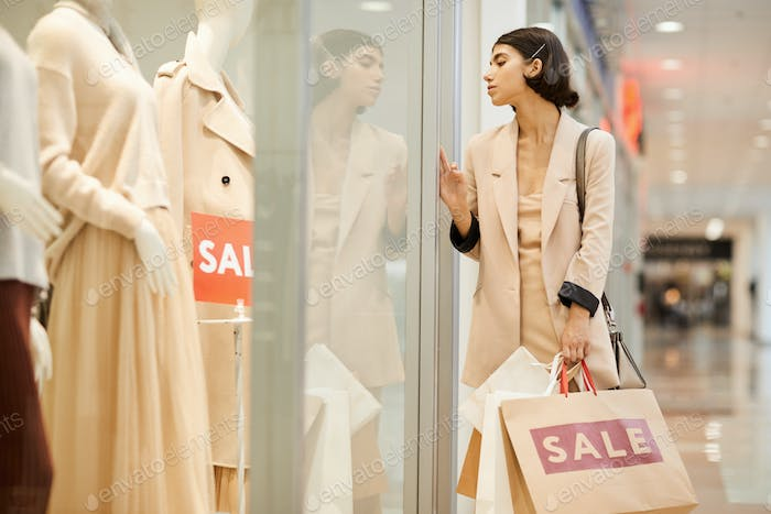 Young Woman Looking at Window Displays in Boutique