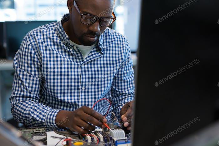 Ingeniero informático reparando la placa base en el escritorio