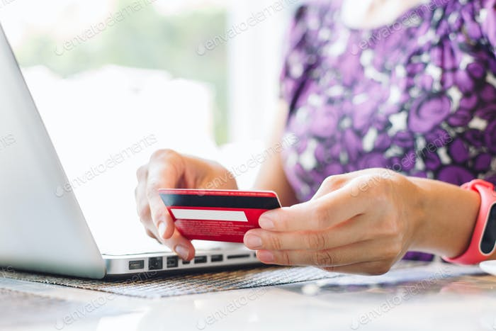 Woman with laptop and credit card in the cafe.