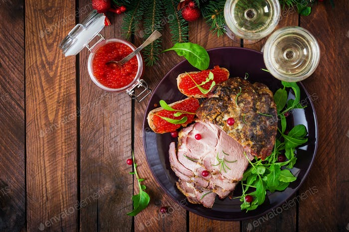 Christmas baked ham and red caviar, served on the old wooden table. Flat lay. Top view