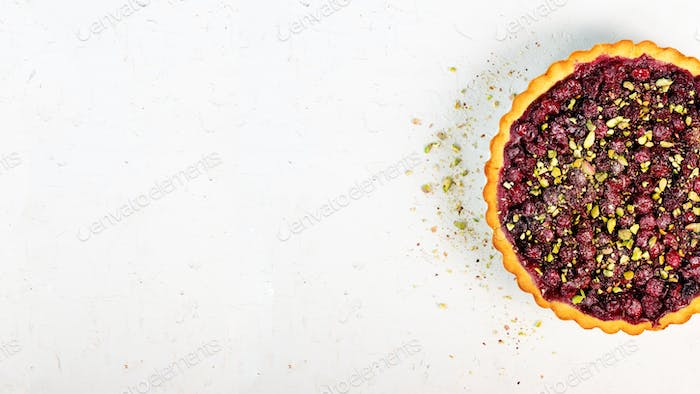 Delicious homamade cranberry, cherry tart with pistachios, powdered sugar on white concrete