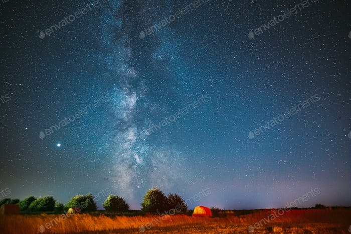 Milky Way Galaxy In Night Starry Sky Above Haystack In Summer Agricultural Field. Night Stars Above