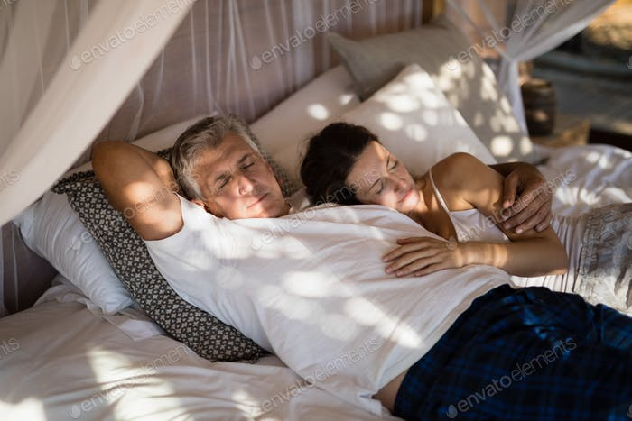 Senior couple sleeping on canopy bed