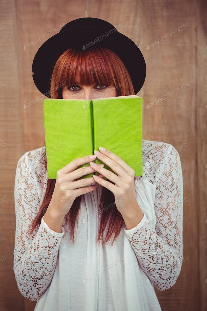 Hipster woman behind a book against wooden background