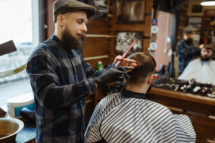 Barber makes a haircut to client, barbershop
