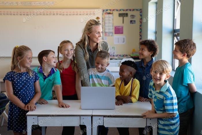 Female teacher using a laptop computer with of schoolchildren