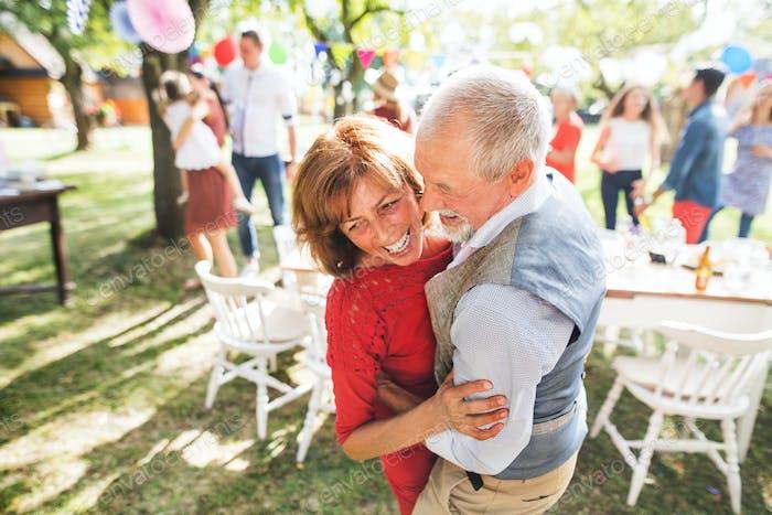 Una pareja de ancianos bailando en una fiesta en el jardín afuera en el patio trasero.