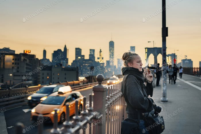 Woman standing on bridge and smoking cigarette, cityscape in background