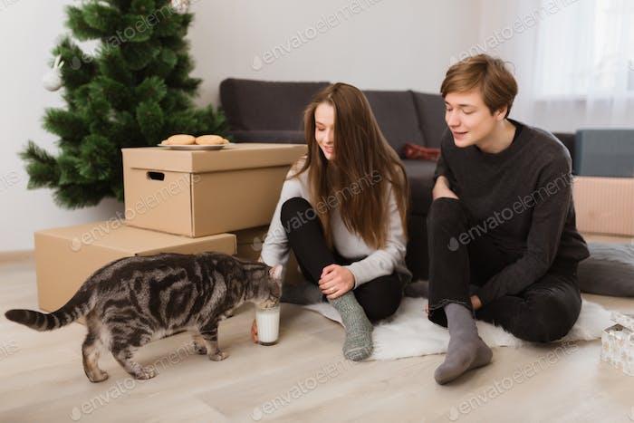 Joven bonita pareja sentado en el suelo en casa y felizmente alimentando gato que beber leche cerca