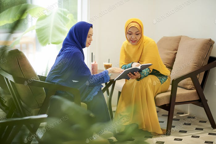Women in hijabs discussing interesting book