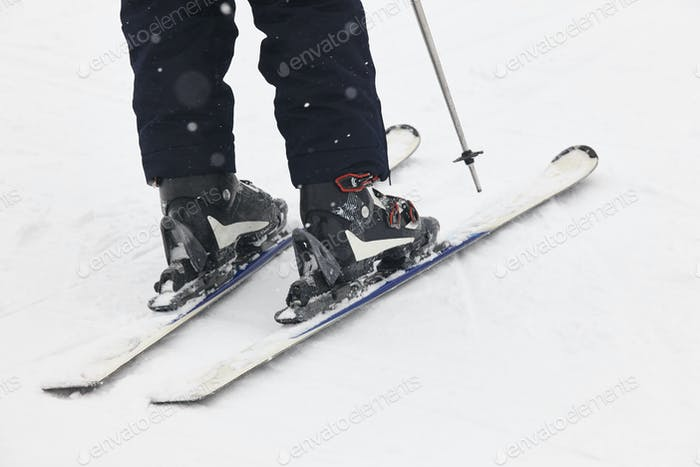 Boots and skis over the snow. Winter sport equipment detail. Horizontal