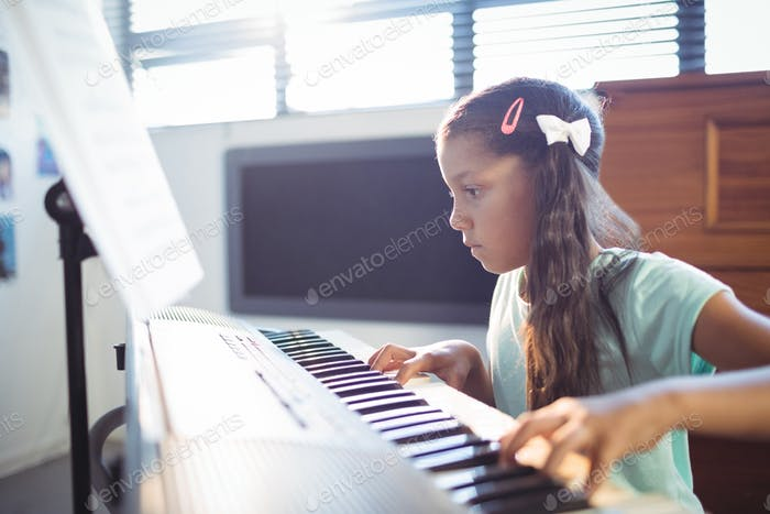 Concentrated elementary girl practicing piano