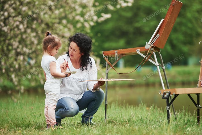 Listen careful. Teaching granddaughter how to paint. In the natural parkland