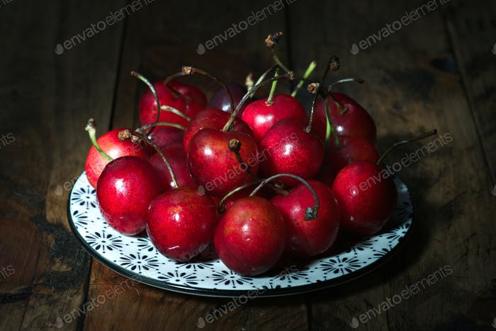 bunch of ripe cherries in porcelain on rustic wood