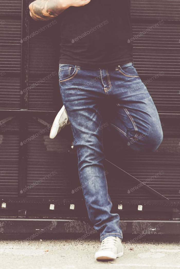 portrait of young fashion handsome hipster man in blue denim jea