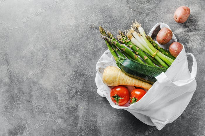 Different vegetables in textile bag on grey