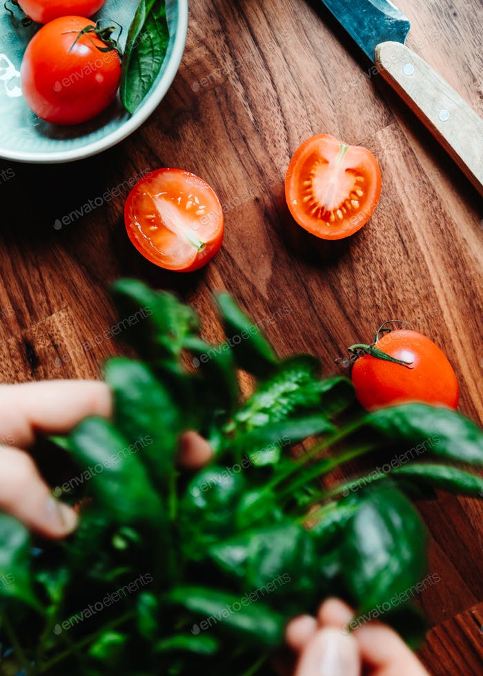 Lifestyle photo of cooking healthy eating with tomatoes and fresh spinach