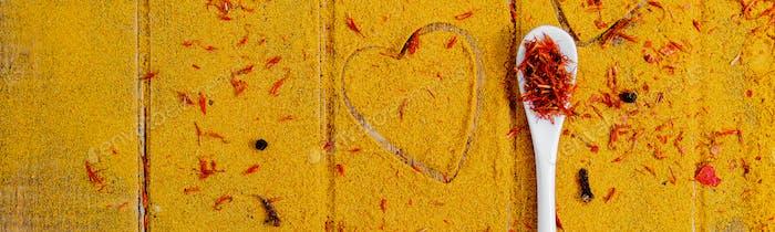 Banner mit Herz von Gewürzen und Gewürzen. Weißer Löffel mit Safran auf Curry-Hintergrund.