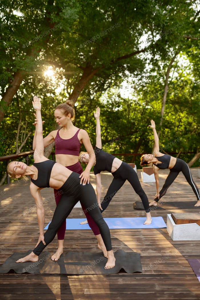 Sportive women on yoga training with instructor