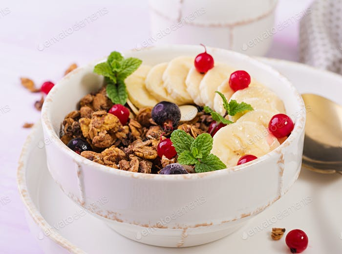 Breakfast. Bowl of homemade granola with yogurt and fresh berries. Table setting. Healthy food.