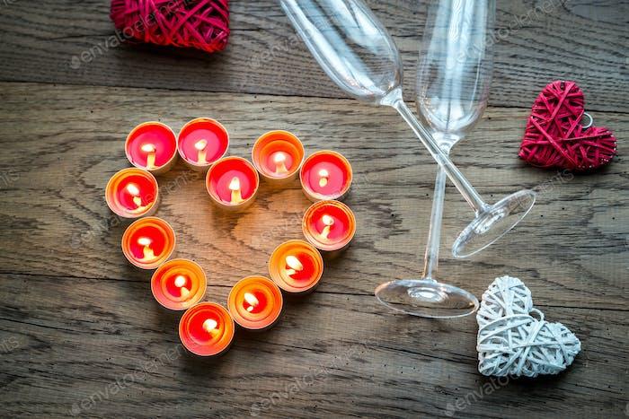 Brennende Kerzen in Form von Herz mit zwei Flöten