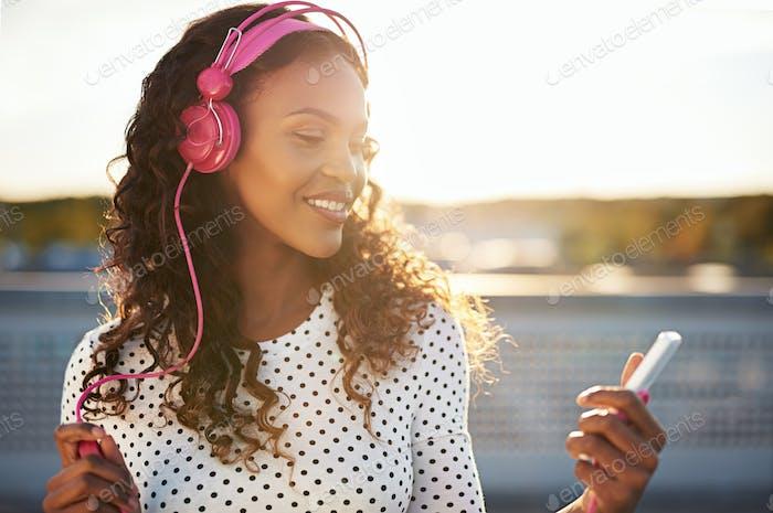 Привлекательная женщина слушает музыку на крыше