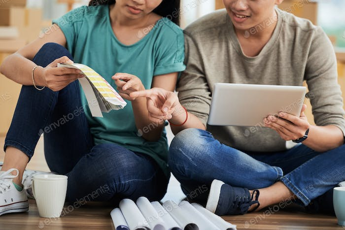 Anonymous couple with tablet choosing color for new apartment