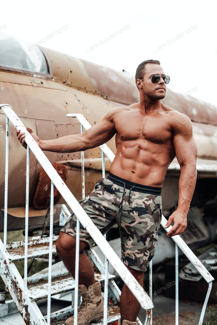 Muscular topless soldier with sunglasses posing near airplane