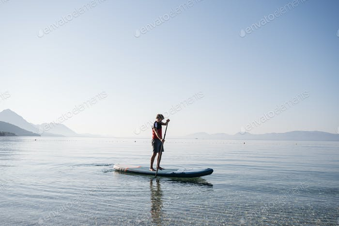 Young man paddling on sup board