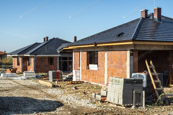 Building a new brick house with black roof. Small houses on cons