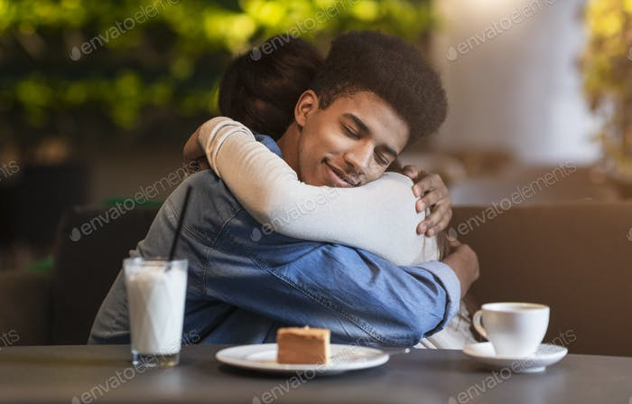 Happy beloved teen couple hugging with affection