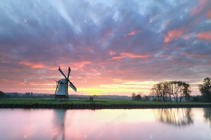 dramatic purple sinrise over windmill by river