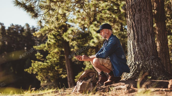 Senior man on hike in nature using a compass
