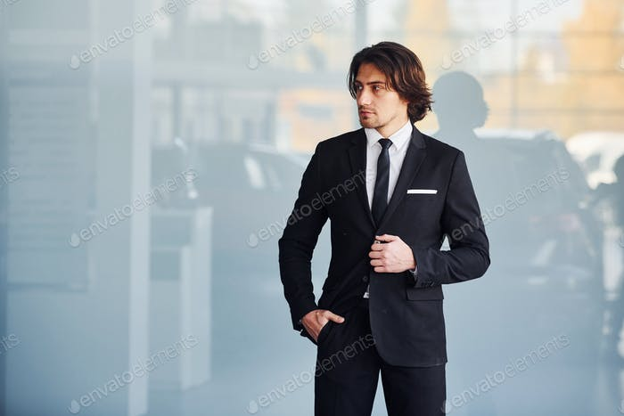 Portrait of handsome young businessman in black suit and tie
