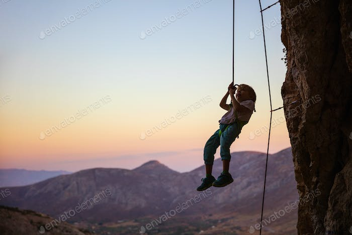 Little boy being lowered down while top rope climbing