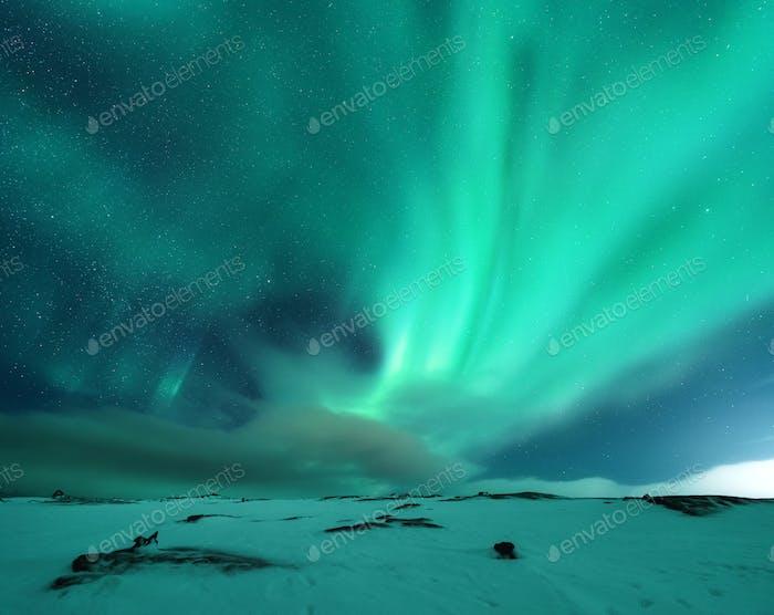 Aurora borealis above the snow covered mountain hill