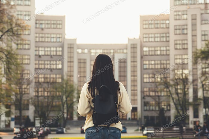Back view of girl walking and looking at the city