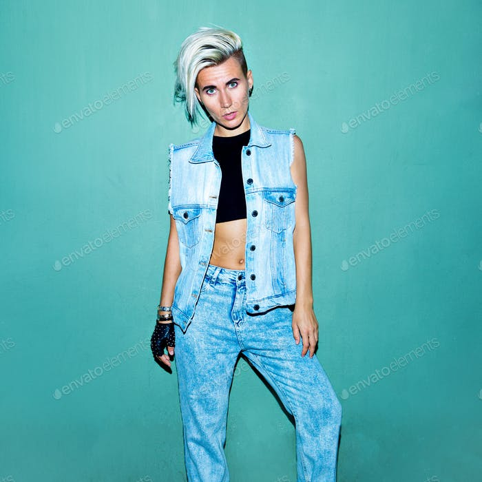 Model in a stylish jeans outfit near a blue wall Street fashion