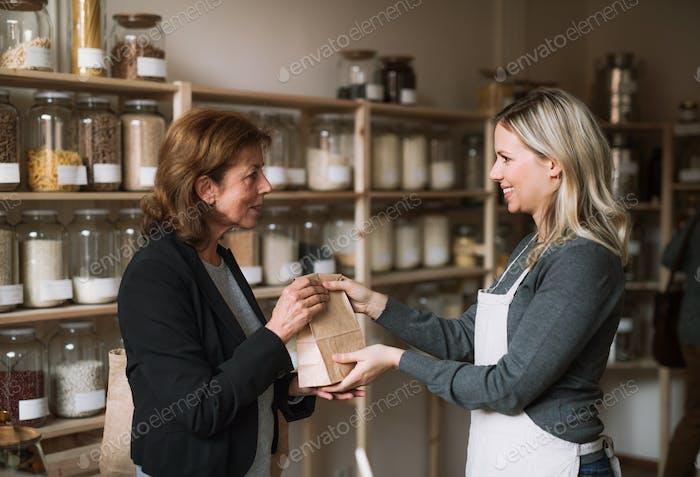 A female shop assistant serving a senior customer in a zero-waste shop.