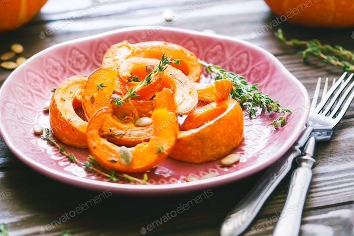 Gebackene Kürbisscheiben mit Thymian auf einem Holzbrett über grauem Tisch. Saisonales Essen vegetarisches Rezept.