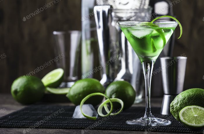 Green alcoholic cocktail martini glass with dry gin, vermouth, liquor, lime zest and ice