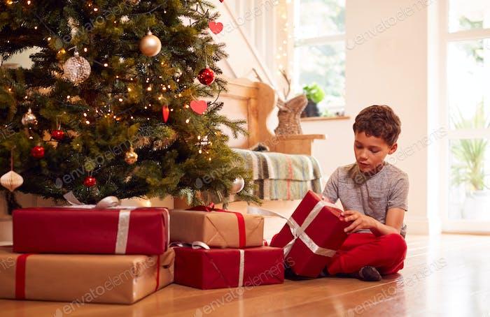 Aufgeregt Junge Eröffnung Geschenke von Baum auf Weihnachten Morgen