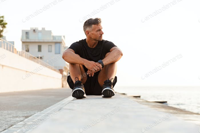Photo of concentrated strong man 30s in tracksuit sitting on par