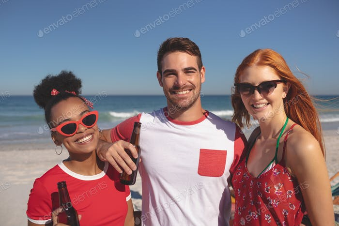 Front view of group of young diverse friends holding beer bottles and looking at camera on the beach