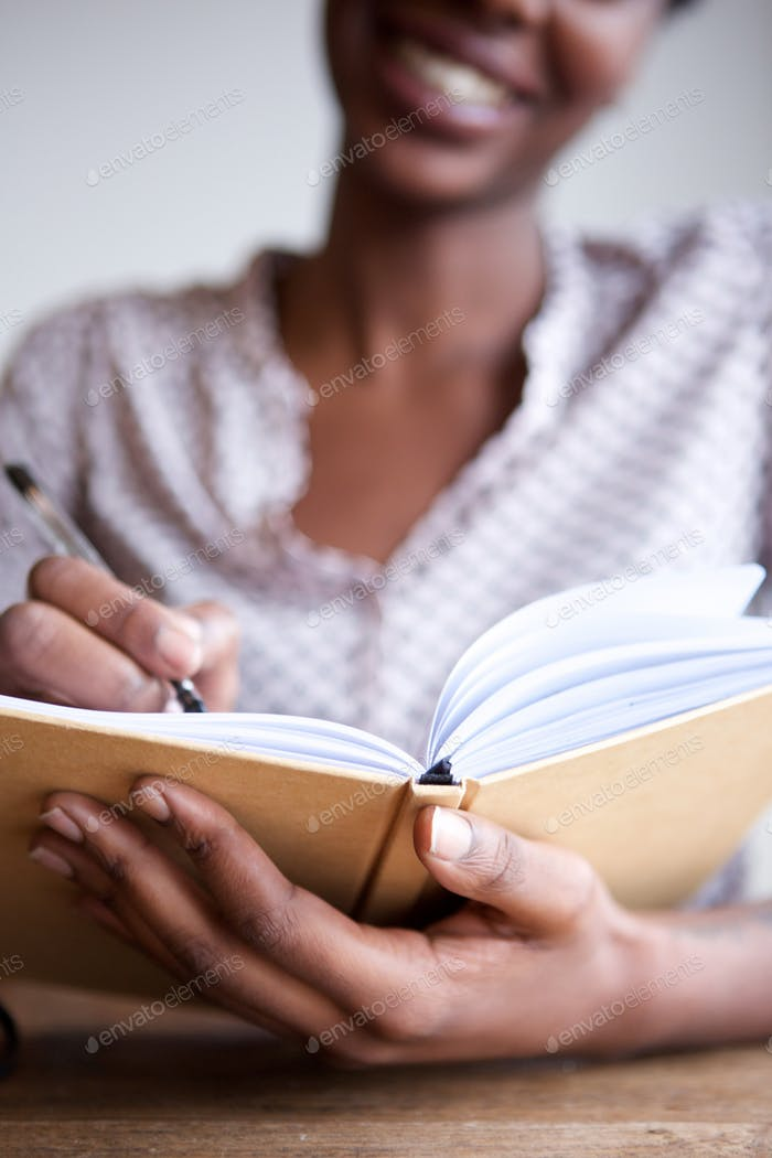 Partial portrait of smiling black female author at home writing in notebook