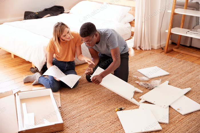 Couple In New Home Putting Together Self Assembly Furniture