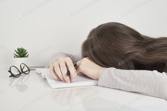 Tired young woman sleeping at table with books, fatigue after school or work