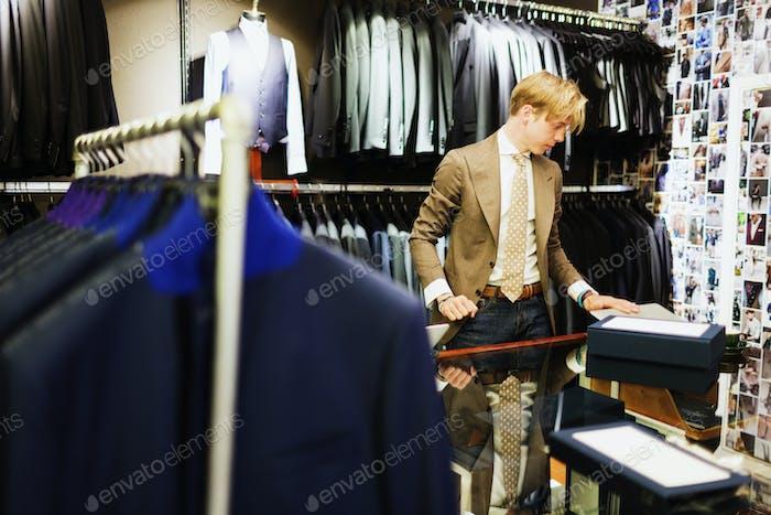 Молодой дизайн-профессионал, работающий в магазине одежды